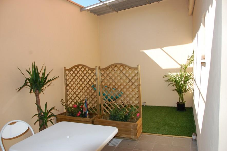 Terrasse ensoleillée du studio avec chaises, table et petit jardin.